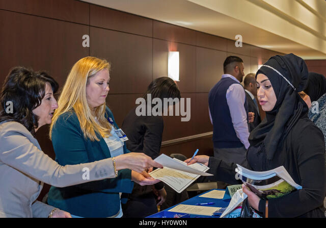 Dearborn, Michigan - Recruiters for Beaumont Hospital talk to a job seekeer at a job fair sponsored by ACCESS, the - Stock Image