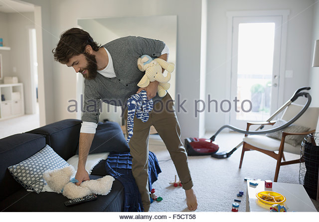 Man picking up toys in living room - Stock Image