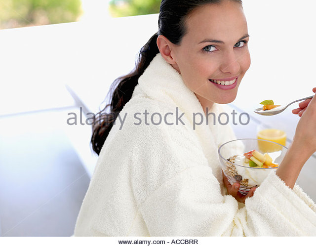 Woman in robe eating healthy breakfast outdoors - Stock Image