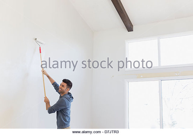 Smiling young man painting wall at home - Stock Image