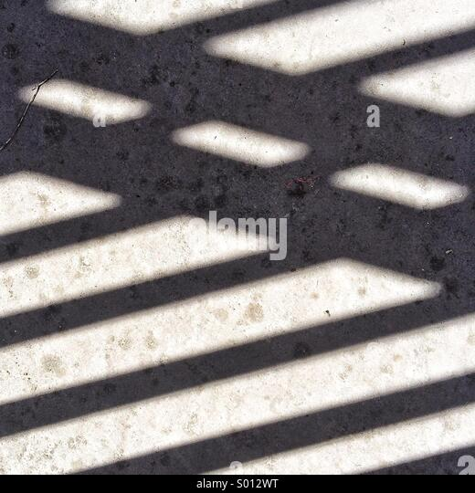 Shadows cast by a gate onto an outdoor paver. - Stock Image