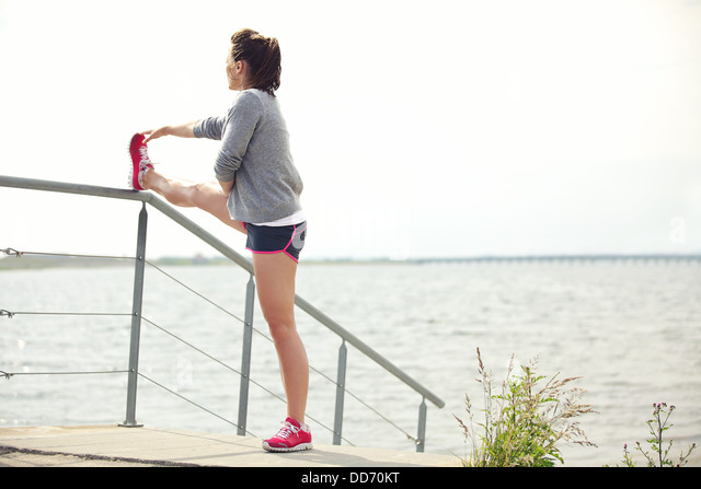 Active young female runner stretching her legs outdoor before running workout. Active lifestyle. - Stock Image