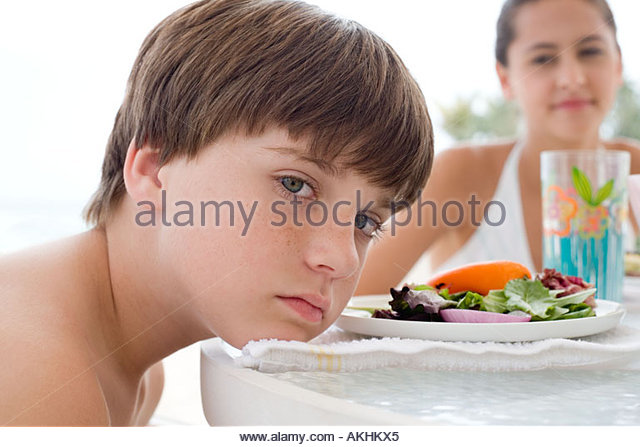 Moody boy at meal - Stock Image