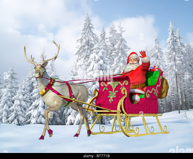 Santa claus driving a sleigh with reindeer, on a snowy ground, with a snowy forest on the background. - Stock-Bilder