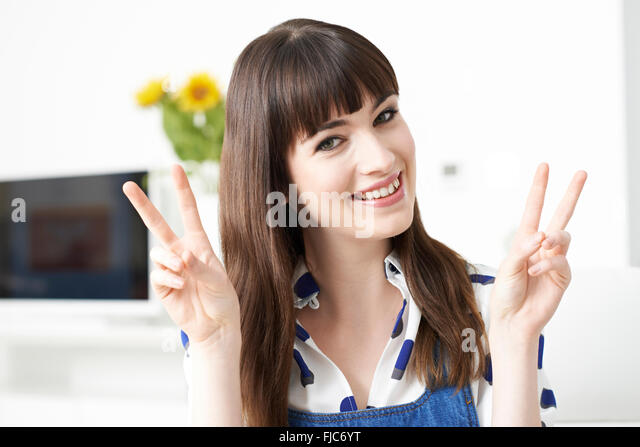 Young Woman Making Peace Gesture With Hands - Stock-Bilder