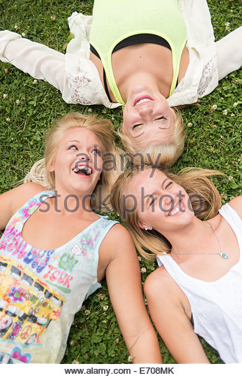 Portrait of three young female friends lying on grass at music festival - Stock Image