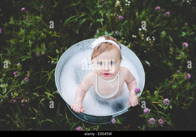 Overhead view of baby girl bathing in a tin bathtub in a wild flower meadow - Stock-Bilder