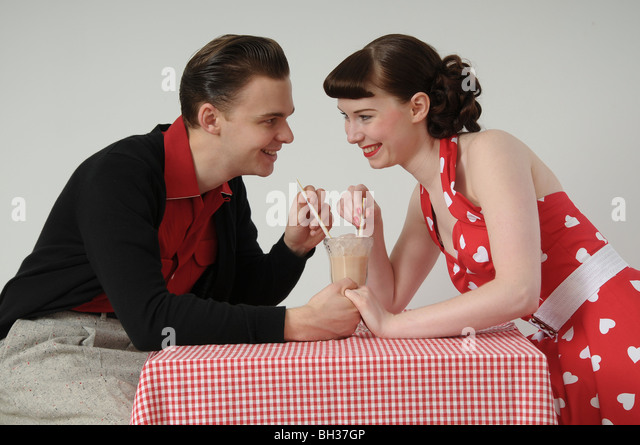 Couple sharing a milkshake in 1950s diner - Stock Image