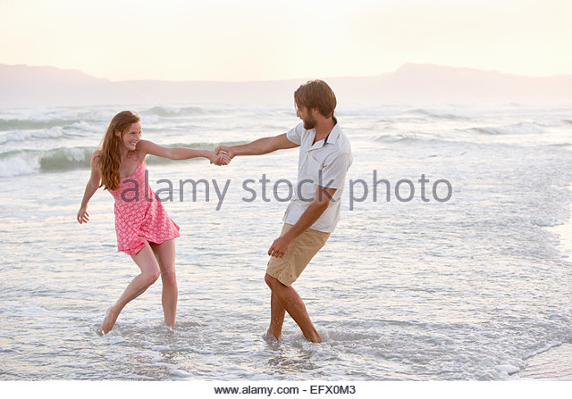 Couple, playfully pulling each other into the sea on sunny beach - Stock-Bilder
