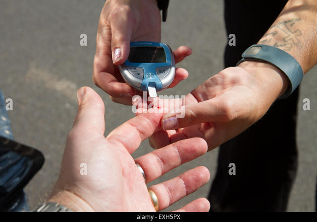 EMT / Paramedic administers blood sugar test in ambulance. - Stock Image