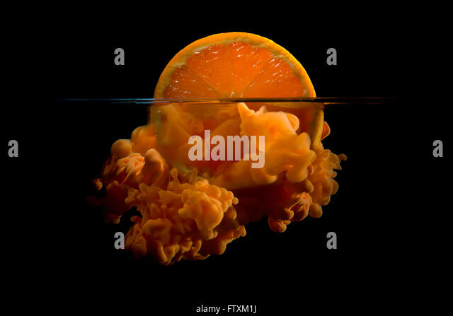 Conceptual sunrise with a slice of orange and acrylic paint - Stock Image