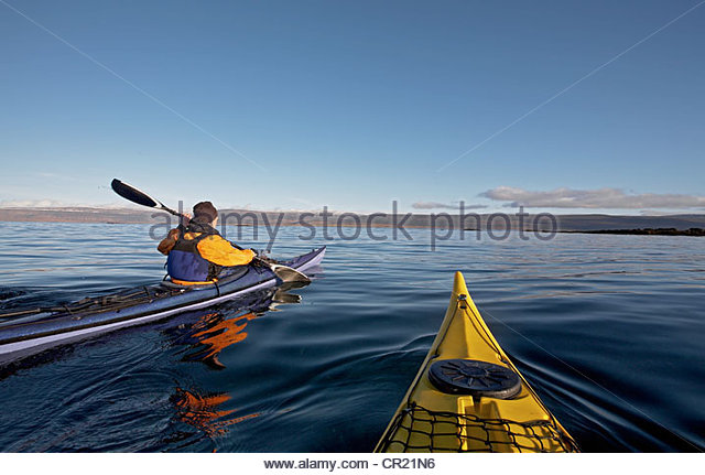 Man rowing canoe in ocean - Stock Image