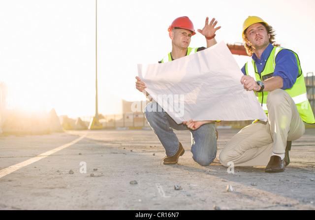 Construction workers reading blueprint - Stock-Bilder