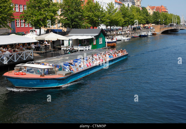 Canal cruise boat in the old Christianshavns Canal in Copenhagen. View at  restaurants along the Oven Gaden Neden - Stock Image