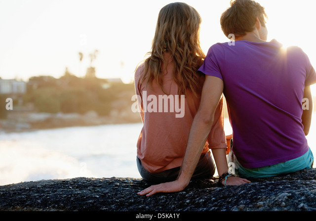 Rear view of young couple sitting at beach - Stock-Bilder