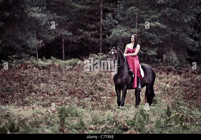 Beautiful Photo of Woman in Pink Dress with Horse in Forest Location - Stock Image