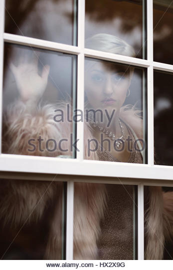 Elegantly dressed blonde woman looking out a window - Stock Image