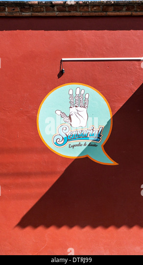 bold slightly macabre graphic design on red wall at shop entrance with stylized aqua thought balloon advertising - Stock Image