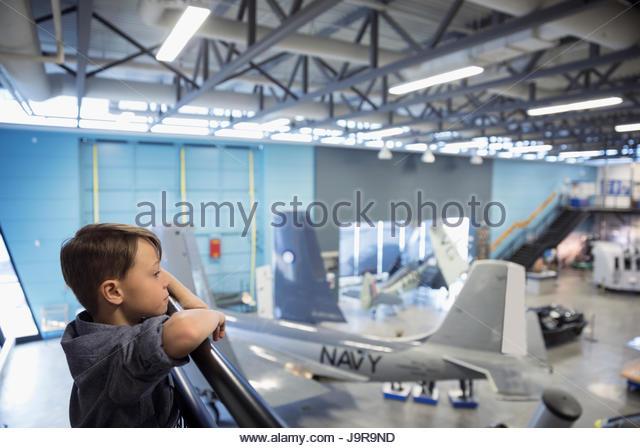 Curious boy watching Naval airplanes in war museum hangar - Stock-Bilder
