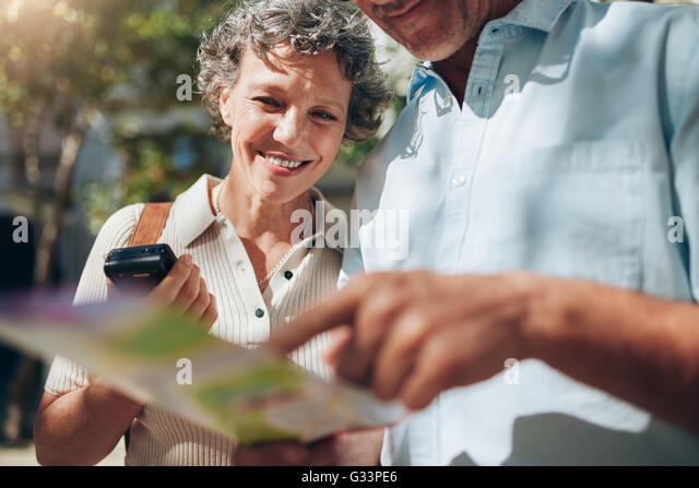 Middle aged couple looking at city map. Happy mature woman with her husband on a summer vacation. - Stock Image