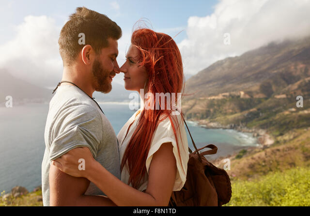 Portrait of young man and woman standing face to face. Affectionate young couple enjoying their love in nature outdoors. - Stock-Bilder