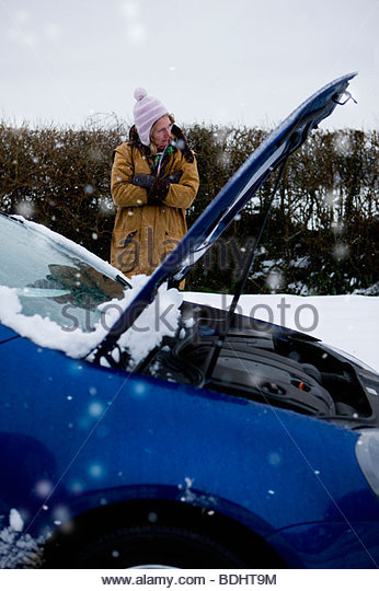 Stranded woman waiting beside car in snow - Stock Image
