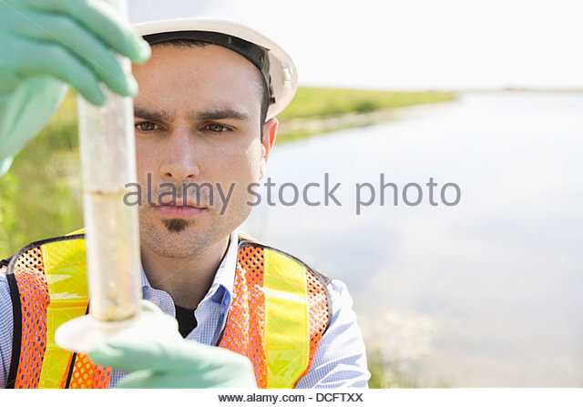 Ecologist taking water samples - Stock Image