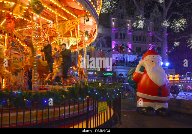 Leicester Square Xmas fairground at night with large Father Christmas - Stock Image