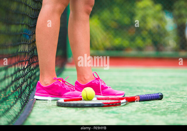 Closeup of shoes with the tennis racquet and ball outdoors on court - Stock-Bilder