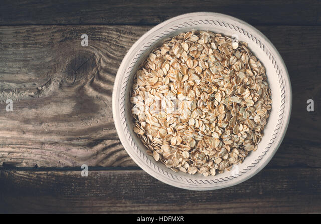 Raw oatmeal in  the bowl on the wooden table top view - Stock Image