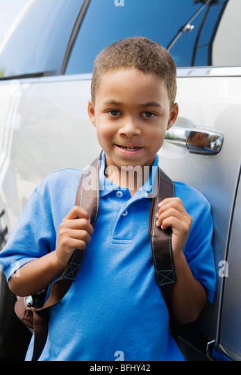 Boy Standing by Minivan - Stock Image