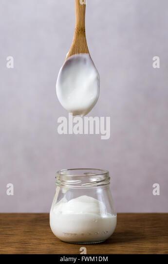 Wooden Spoon Above Yogurt Jar On Table - Stock Image