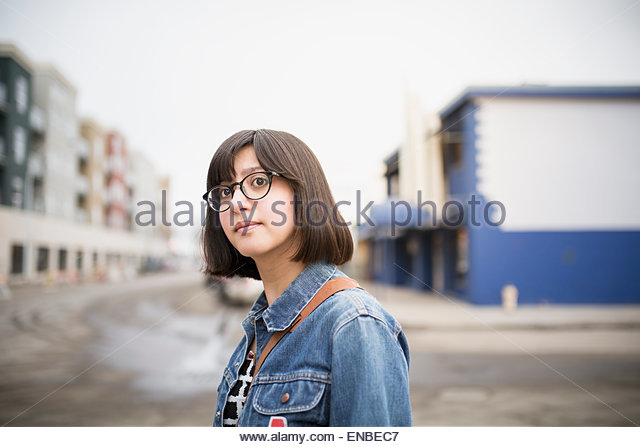 Portrait of confident woman in denim jacket - Stock Image