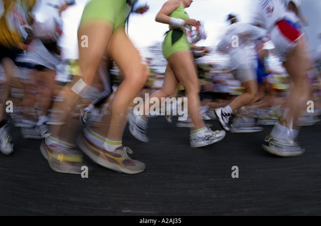 The blur of a crowd of runner s legs distorted by a wide angled lens during the London Marathon - Stock Image