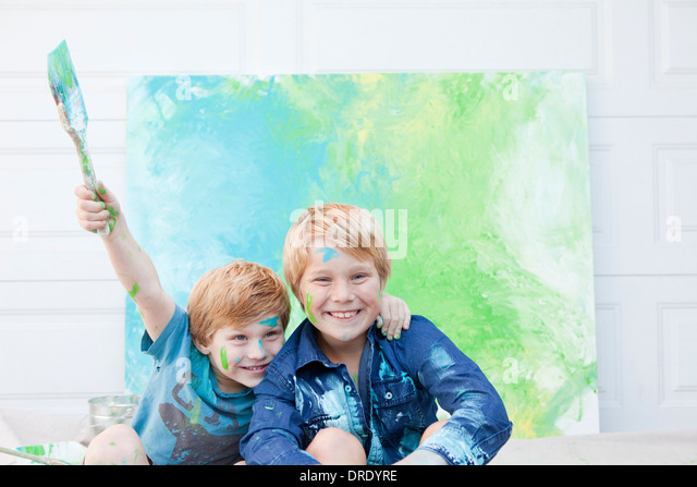 Brothers laughing in front of painting - Stock Image