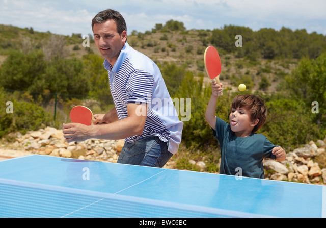 Father and son playing table tennis - Stock Image