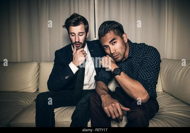Two young men sitting on sofa - Stock Image