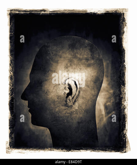 Grainy and gritty image of a man's head with ear in spotlight. - Stock-Bilder