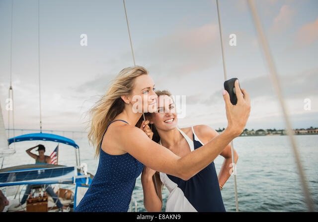 Friends photographing themselves on sailing boat - Stock Image