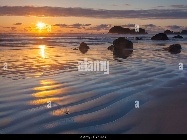 Bandon State Park, Oregon: Sunset reflections at low tide with silhouetted seastacks at Bandon Beach - Stock Image