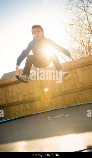 9 year old boy jumping on a trampoline in his garden. - Stock Image