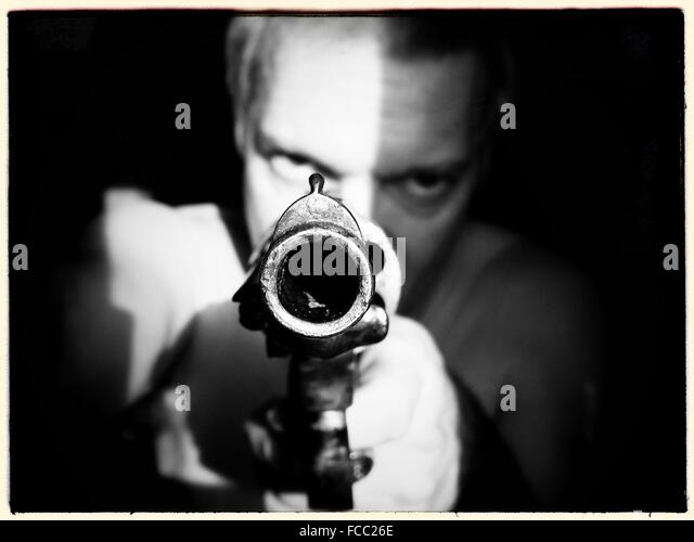 Man Aiming Gun At Camera - Stock Image