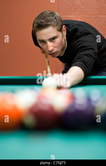 A young man lines up his shot as he breaks the balls for the start of a game of billiards. Shallow depth of field. - Stock-Bilder