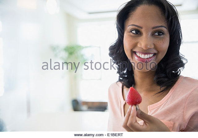 Smiling woman eating strawberry - Stock Image