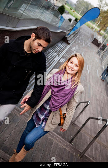 Happy young couple walking up steps in town - Stock-Bilder