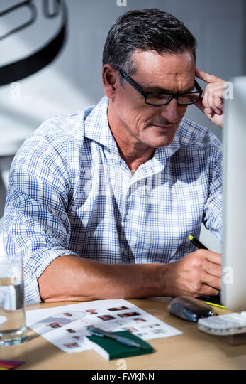 Tense man working on his graphics tablet - Stock Image