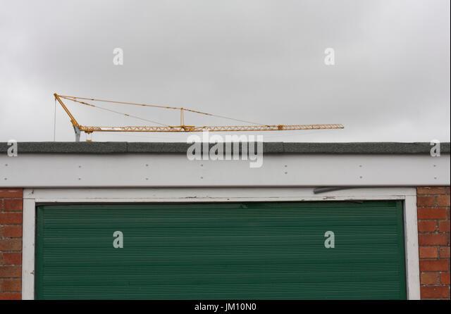 Construction crane behind a garage door - Stock Image