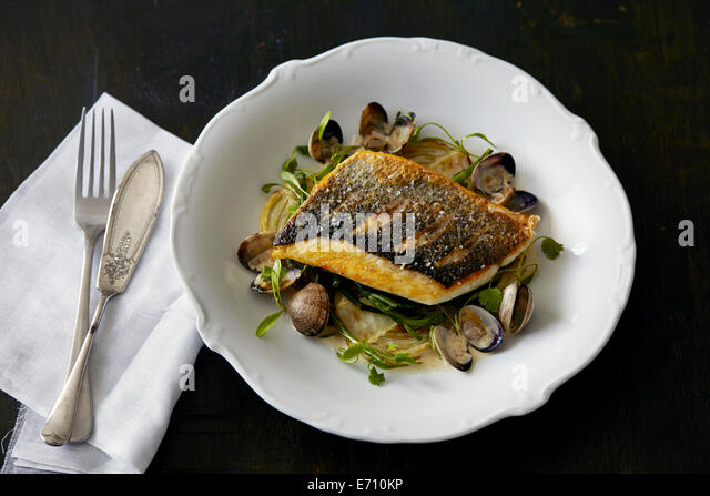 Plate of fish and clams with herbs - Stock Image
