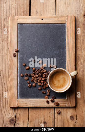 Coffee cup with coffee beans on vintage slate chalk board - Stock Image