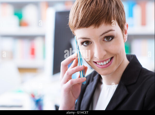 Smiling confident businesswoman on the phone, she is calling with a smart phone - Stock Image